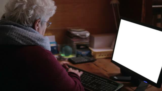 Velha mulher escrevendo no computador