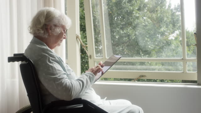 old woman using digital tablet on wheelchair - only senior women stock videos & royalty-free footage