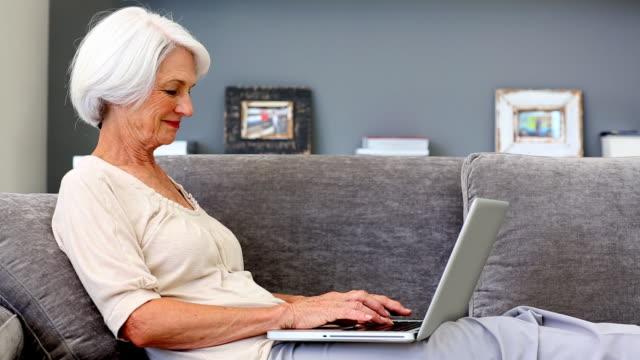 vídeos y material grabado en eventos de stock de old woman using laptop on couch - cabello canoso
