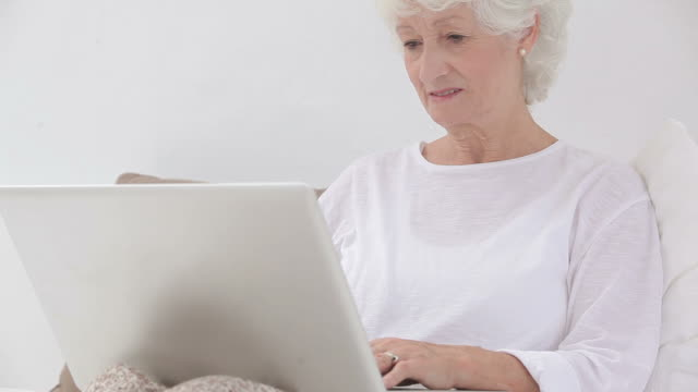 old woman using laptop - silver surfer stock videos & royalty-free footage
