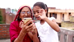 HD:  Old woman using mobile with her granddaughter