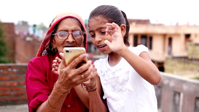 hd:  old woman using mobile with her granddaughter - india video stock e b–roll
