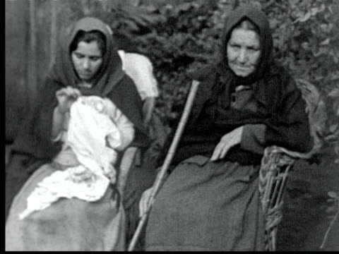 old woman w/ crutch sits in chair next to young woman doing embroidery / funchal madeira - 1925年点の映像素材/bロール