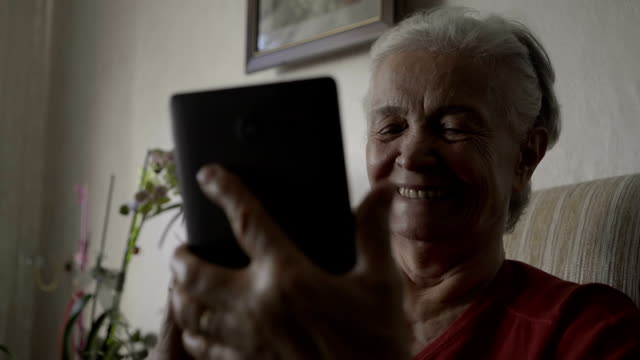 old woman waves while having a  video call on digital tablet - moving image stock videos & royalty-free footage
