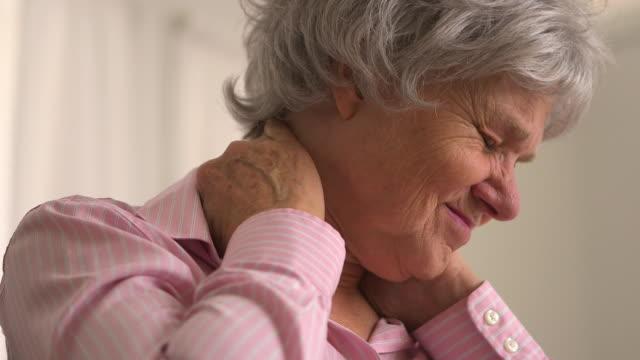 vídeos de stock e filmes b-roll de old woman with neck pain - dor no pescoço