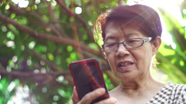 Gammal kvinna med smartphone med videochatta med sin familj