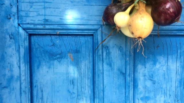 vídeos y material grabado en eventos de stock de vieja puerta de madera con colgante secado de cebollas - cebolla