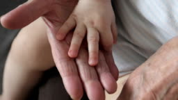 Old wrinkled hands touching the baby's soft hands.
