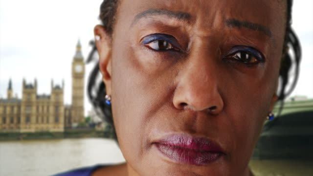 older african american woman near big ben looking sadly into the distance - big ben点の映像素材/bロール