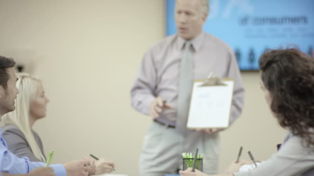 older aged male leader presenting business ideas to his team - fatcamera stock videos & royalty-free footage