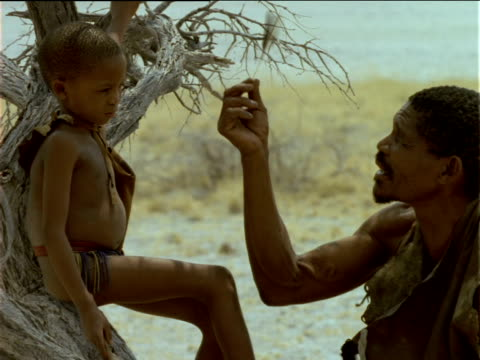 older basarwa tribesman telling story as child listens - tradition stock-videos und b-roll-filmmaterial