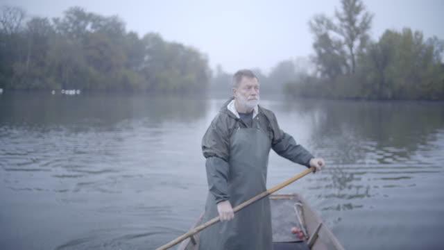 older bearded fisherman in rain gear paddles boat alone down rural river - fisherman stock videos & royalty-free footage