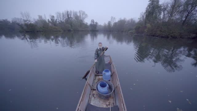 雨具で古いのひげを生やした漁師のパドル ボート農村部の川を単独で - 男漁師点の映像素材/bロール
