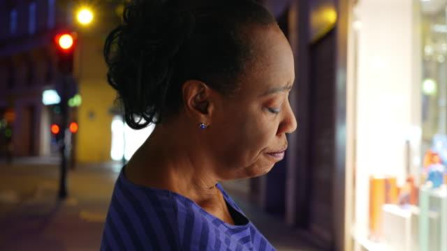 older black woman looks sadly into store window at night - profil redigerat segment bildbanksvideor och videomaterial från bakom kulisserna