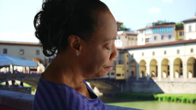 older black woman stands near ponte vecchio bridge looking sadly at the river - ponte点の映像素材/bロール