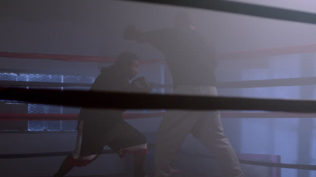 A boxer practices with his coach in boxing ring.