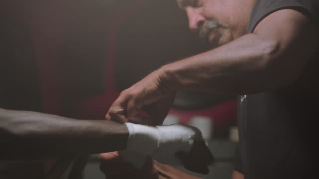 cu. older boxing coach wraps young boxer's hands with white wrapping tape before a fight in a professional boxing gym - boxing ring stock videos & royalty-free footage