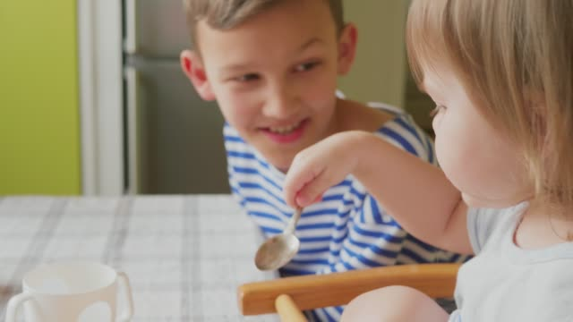 older brother amusing little sister during breakfast in kitchen - happy meal stock videos & royalty-free footage
