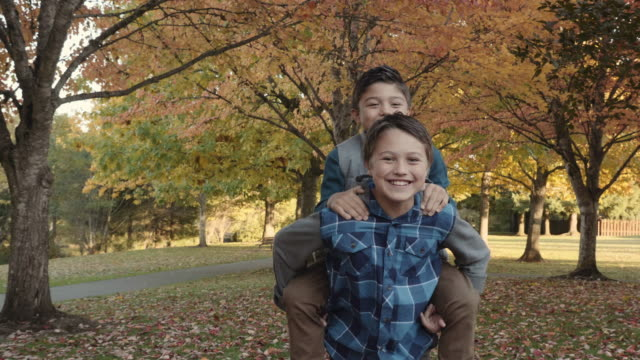 older brother giving his younger brother a piggy back ride in the park - sibling stock videos and b-roll footage