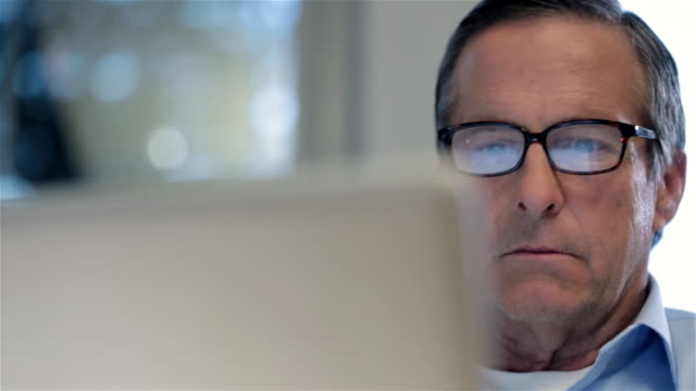 older businessman scans laptop-computer screen in private corporate office dolly-shot - spectacles stock videos & royalty-free footage