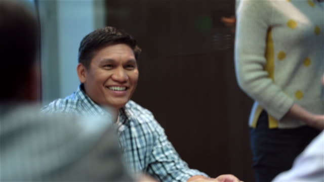 Older businessman smiles, listens to presentation and discussion in corporate boardroom