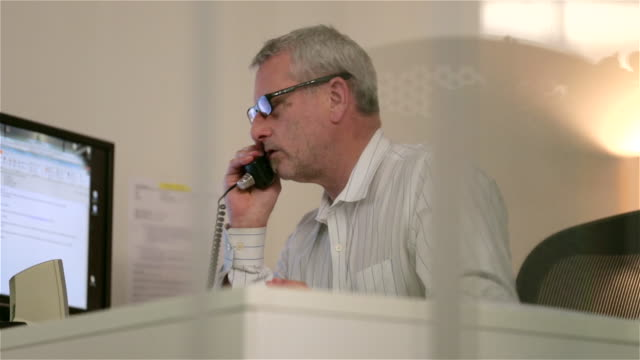 older businessman talks on phone, people cross in foreground (dolly shot) - customer service representative stock videos & royalty-free footage
