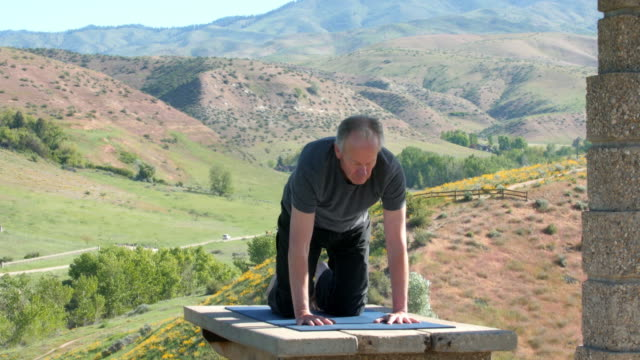 older caucasian man performing yoga on picnic table - sun salutation stock videos & royalty-free footage