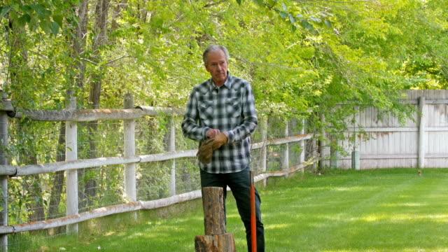 Older Caucasian man splitting wood in backyard