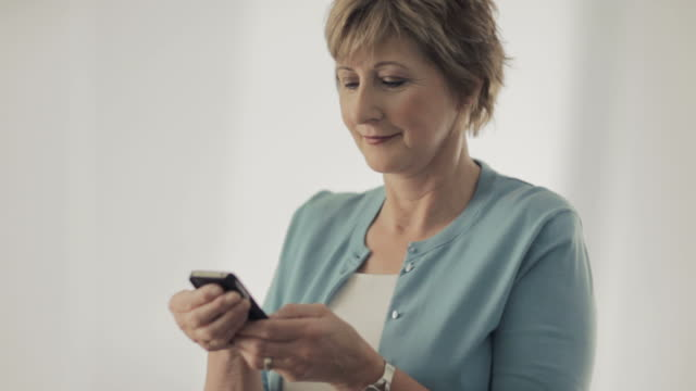 older caucasian woman looking at cell phone and smiling - cardigan sweater stock videos & royalty-free footage