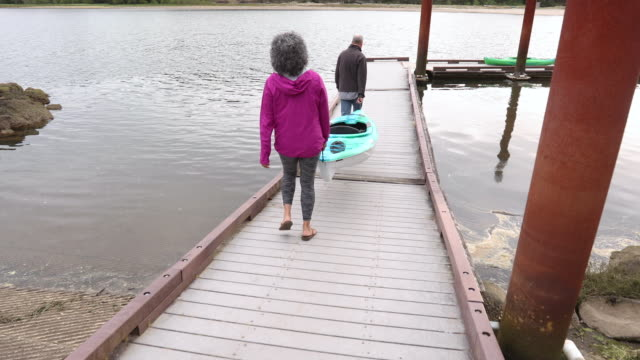 older couple carrying kayak down to dock - two people stock videos & royalty-free footage