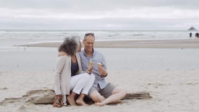 older couple eating ice cream on a log at the beach - pacific islander couple stock videos & royalty-free footage
