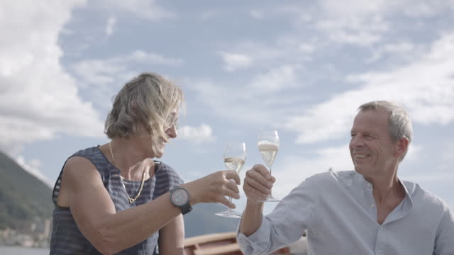 older couple enjoying champagne on a boat on a lake - couple relationship stock videos & royalty-free footage