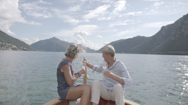 older couple enjoying champagne on a boat on a lake - desire stock videos & royalty-free footage