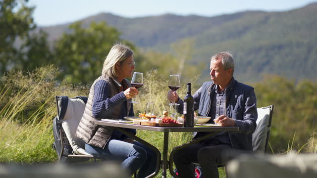 vídeos de stock e filmes b-roll de older couple having an outdoor meal enjoying wine with mountains behind - casaco curto com mangas