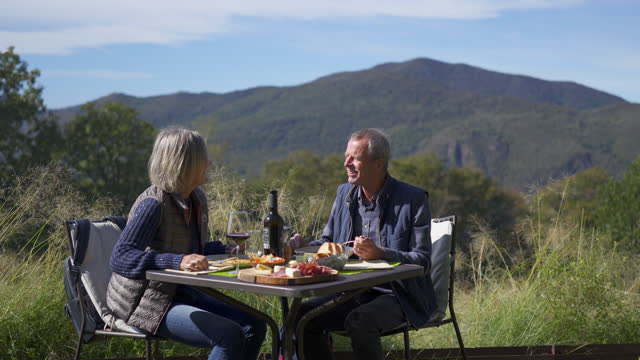 older couple having an outdoor meal enjoying wine with mountains behind - social grace stock videos & royalty-free footage