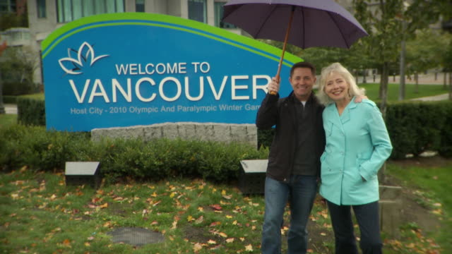 MS TU Older couple holding umbrella and smiling in front of 'Welcome to Vancouver sign' / Vancouver, British Columbia, Canada