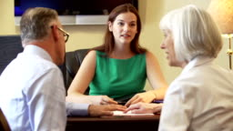 Older Couple Talking To Financial Advisor In Office