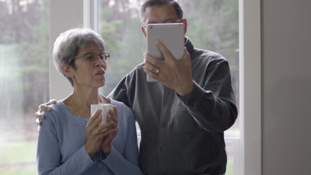 Older Couple Using Tablet to Video Chat with Family from Their Home
