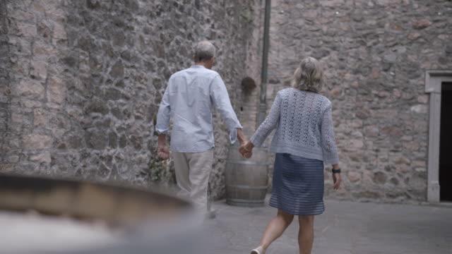 älteres paar zu fuß durch eine steinburg - schlossgebäude stock-videos und b-roll-filmmaterial