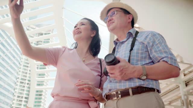 stockvideo's en b-roll-footage met oudere paren genieten van reizen en het nemen van foto's - zelfportret fotograferen