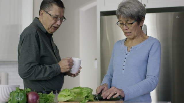 Older Ethnic Couple Chopping Vegetables in a Kitchen