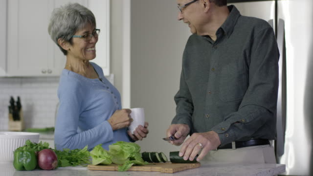 Older Ethnic Man Chops Vegetables While Chatting with His Wife in the Kitchen