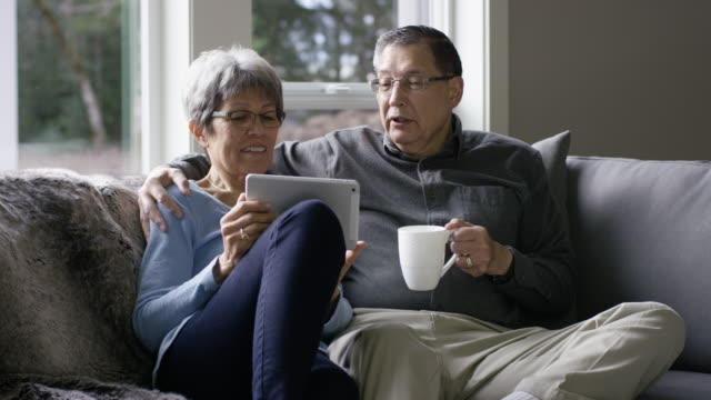 Older Ethnic Woman Using a Tablet While Snuggling with Her Husband