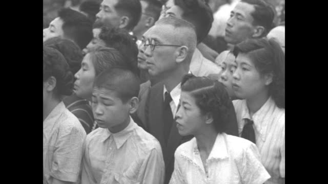 Older Japanese women kneel while children stand all watching for funeral cortege of Empress Teimei mother of Japanese Emperor Hirohito / carriage...