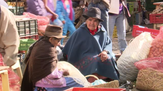 vídeos de stock e filmes b-roll de older ladies in ponchos stilling at stall embroidering, villa de leyva market, villa de leyva, boyacã¡ department, colombia - colômbia