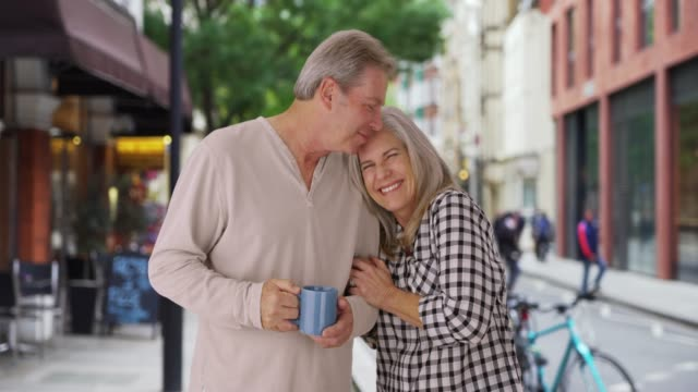 older loving caucasian couple snuggles on london sidewalk - weitere themen stock-videos und b-roll-filmmaterial
