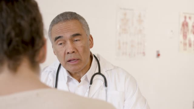 older male doctor talking to female patient - fatcamera stock videos & royalty-free footage