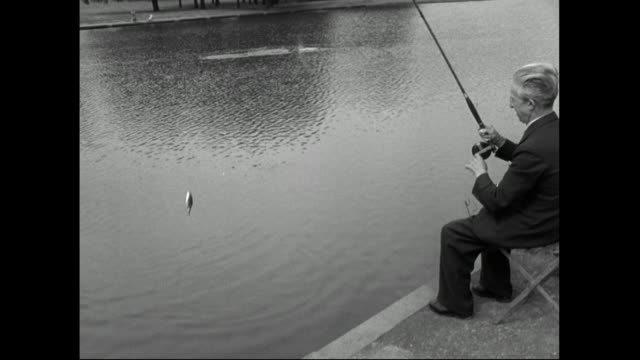 older male fisherman reels in a fish;1951 - archival stock videos & royalty-free footage