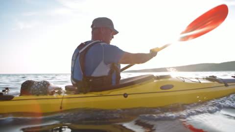 vídeos y material grabado en eventos de stock de slo mo mayores kayakista hombre remando en su kayak de mar en el sol - pasatiempos