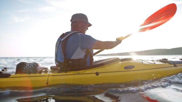 slo mo older male kayaker paddling his sea kayak in the sun - hobbies stock videos & royalty-free footage